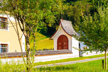 Wall Mural - Small chapel near church in village of Going am Wilden Kaiser on beautiful sunny summer day, Tirol, Austria