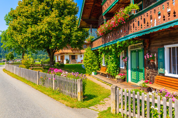 Wall Mural - Stree with typical wooden alpine houses decorated with flowers Reith bei Kitzbuhel village on sunny summer day, Tirol, Austria