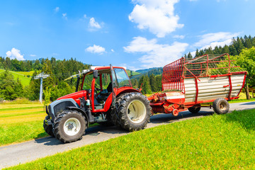 Wall Mural - Red tractor on rural road with green farming fields in near distance on sunny summer day, Tirol, Austria