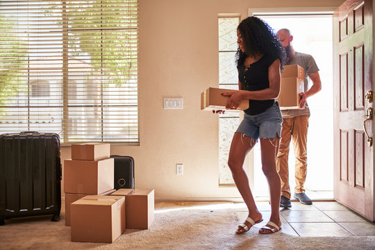 interracial couple moving into new house with boxes