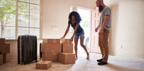 interracial couple moving into new house with boxes Wall mural