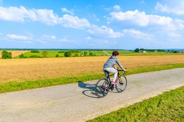 Wall Mural - Young woman riding bicycle on rural road in spring landscape of Burgerland near Strem village, Austria