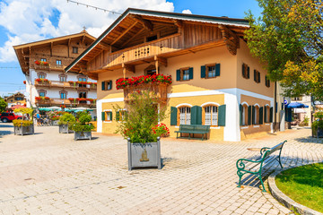 Wall Mural - Typical alpine houses decorated with flowers on square of Kirchberg village on sunny summer day, Tirol, Austria