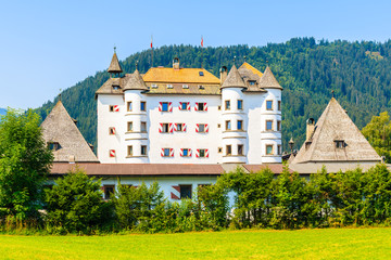 Wall Mural - White facade of castle on green meadow in Reith bei Kitzbuhel village in summer season, Tirol, Austria