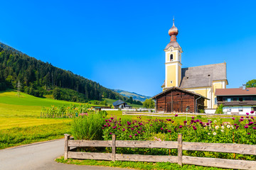 Wall Mural - Sunflowers on green field and church in Going am Wilden Kaiser village on beautiful sunny summer day, Tirol, Austria