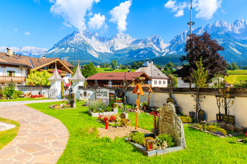 Wall Mural - TIROL, AUSTRIA - JUL 30, 2018: Church cemetery and traditional alpine houses in village of Going am Wilden Kaiser on beautiful sunny summer day with Alps mountains in background, Tirol, Austria.