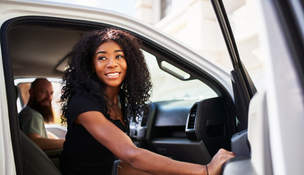 young african american woman getting out of truck and opening door