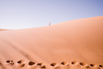 Windswept sand dunes with distant lone figure and camel footprints , in the Sahara Desert, Morocco, Africa