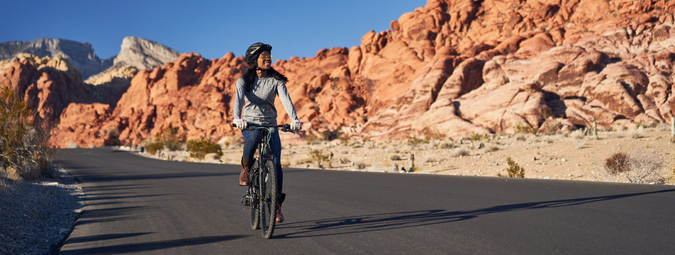 fit african american woman riding bicycle on road in red rock canyon park panorama