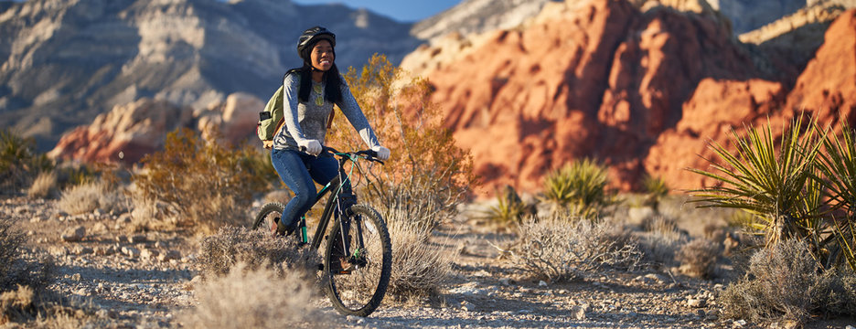 fit african american woman riding bicycle offroad in red rock canyon park panorama