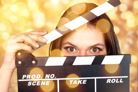 Young woman with movie clapper isolated