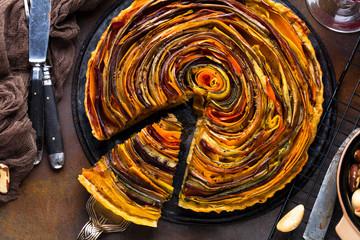 Spiral Gemüse Tarte auf bunt dekoriertem tisch.