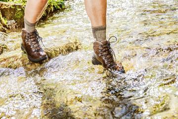 Male legs, in waterproof sports hiking boots, walking on water(river)