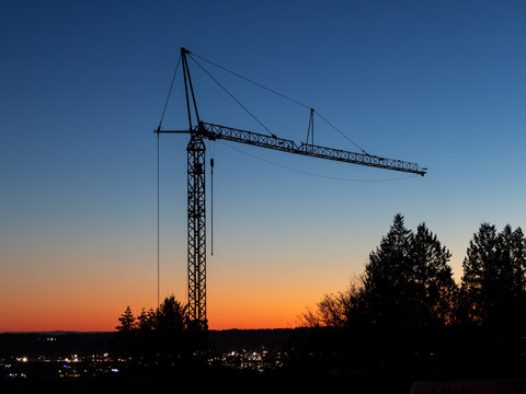 Tall construction crane silent in the sunset