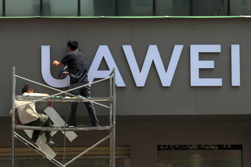 Workers put up a sign for a new Huawei store under construction in Kunming