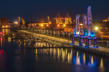 Illuminated old port cranes on a boulevard in Szczecin City at night