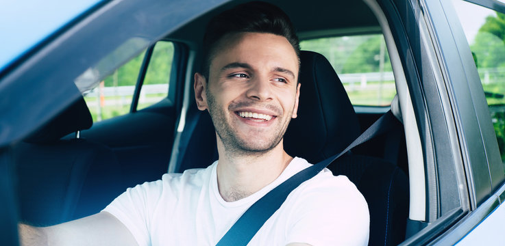Happy handsome young man driving his car and smiling. Excited driver in urban city. Electro car, vehicle of future.