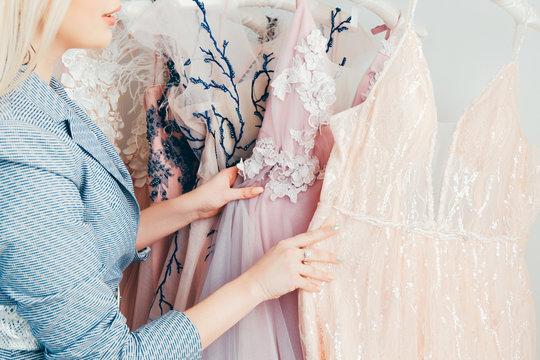 Modern fashion showroom. Cropped shot of woman choosing designer luxury evening gown.