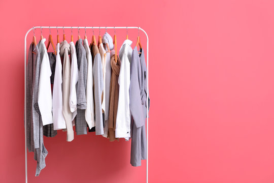 Rack with stylish clothes on color background