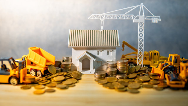 House, crane and construction truck models with gold coins spilling on wooden table. Real estate development or property investment. Home mortgage loan rate. Construction industry business concept