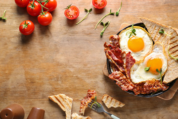 Frying pan with tasty eggs, bacon and toasts on table