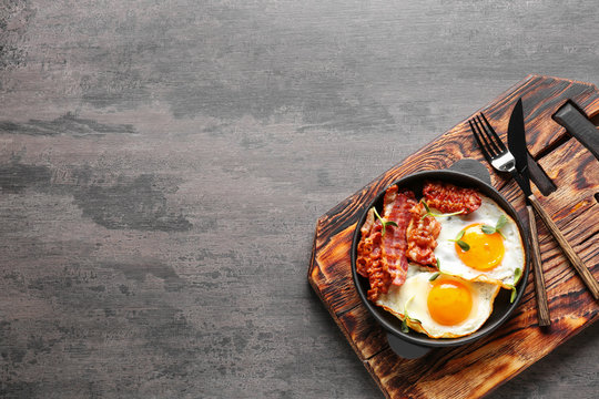 Frying pan with tasty eggs and bacon on grey background