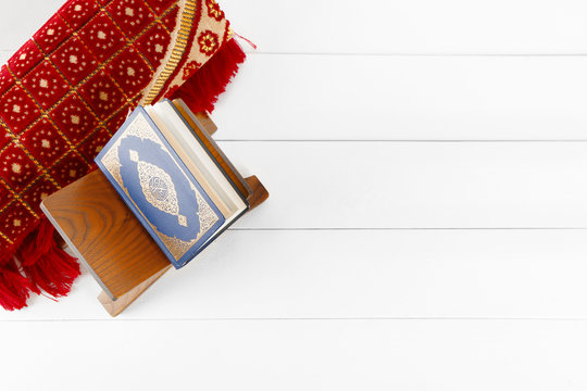 Muslim prayer mat and Koran on white wooden table