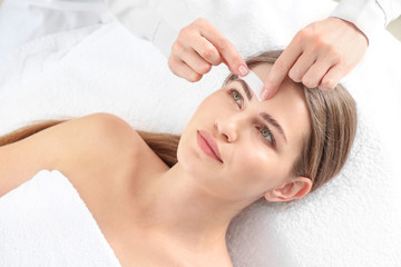 Young woman undergoing eyebrows epilation in beauty salon