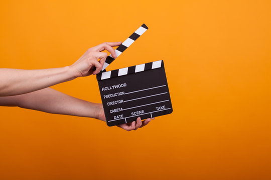 Woman holding professional film slate, movie clapper board in studio over yellow background