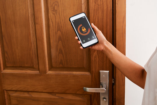 Close-up of woman standing near the wooden door and locking it with online application on her smartphone