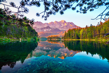 Great summer morning on the Eibsee lake with Zugspitze mountain range. Sunny outdoor scene in...