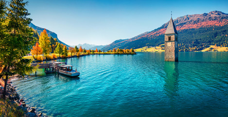 Panoramic autumn view of Tower of sunken church in Resia lake. Sunny morning scene of Italian Alps, South Tyrol, Italy, Europe. Traveling concept background.