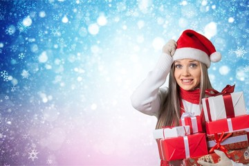 Young girl with christmas gifts on light blurred background