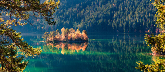 Amazing autumn scene of Eibsee lake. Sunny morning view of small island on bottom of the Zugspitze peak, Bavaria, Germany, Europe. Beauty of nature concept background. Wall mural
