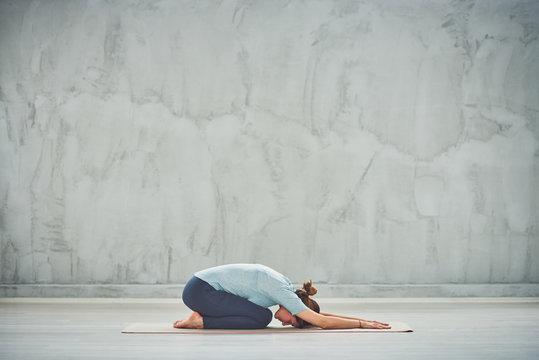 Fit Caucasian brunette doing Extended Child's yoga exercise.