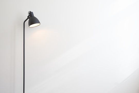 Standing black lamp over white wall