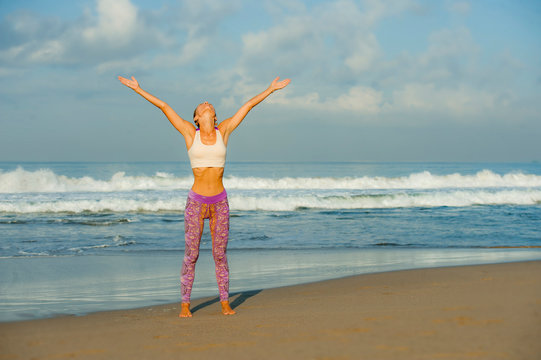 young happy and attractive woman in yoga pants stretching and doing flexibility and meditation exercise at beautiful beach in wellness and healthy natural lifestyle