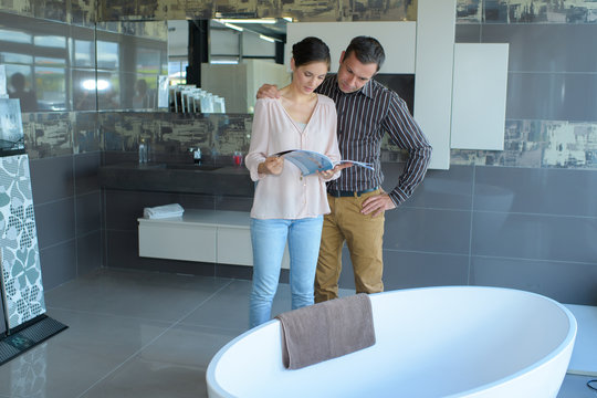 couple looking at oval bath in bathroom store