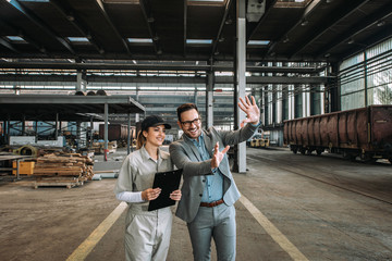 Investor talking to a female employee at large train repair station. Wall mural
