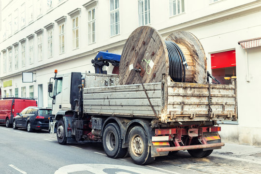 Truck delivering heavy supply electric cable reel at city street