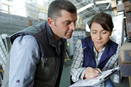 woman with clipboard standing back at warehouse