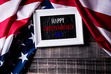 Top view of white picture frame with Flag of the United States of America on wooden background.  Independence Day USA, Memorial.