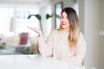 Young beautiful woman wearing winter sweater at home smiling cheerful presenting and pointing with palm of hand looking at the camera.