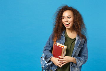 Young african american girl teen student in denim clothes, backpack hold books isolated on blue...