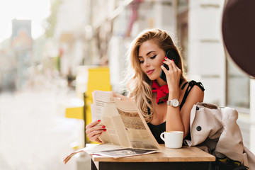 Pleased young woman with tanned skin holding smartphone and reading article during coffee-break. Outdoor portrait of smiling girl in wristwatch talking on phone in cafe in morning.