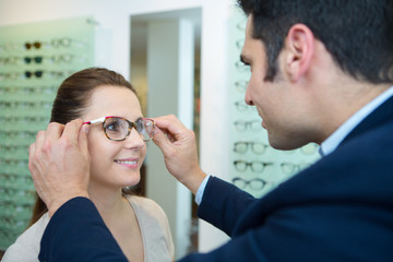 optician fitting new glasses for female patient