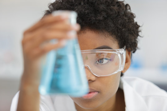 woman in glasses looks at the blue liquid in flask