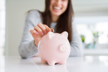 Young woman smiling putting a coin inside piggy bank as savings for investment
