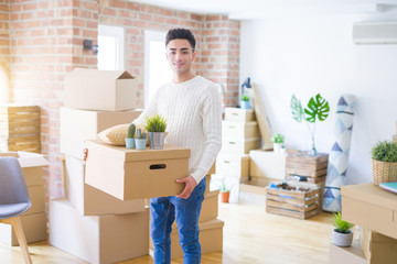 Young man smiling holdig cardboard box, happy moving to a new house