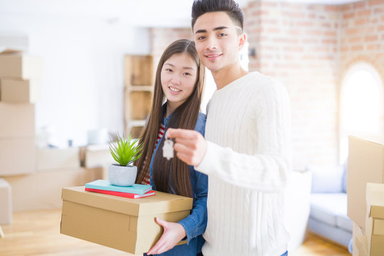Young asian couple holding keys of new house, smiling happy and excited moving to a new apartment